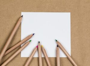 child colouring pencils and paper